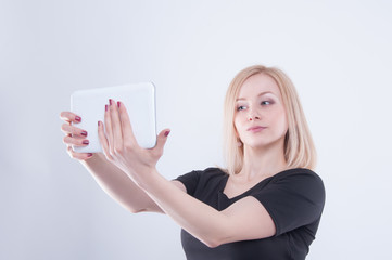 Woman making selfie with tablet on white isolated background. Close up of young blonde beautiful girl in black dress looking in white tablet in her hands.