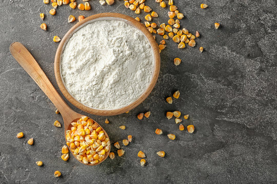 Spoon with kernels and corn starch in bowl on table