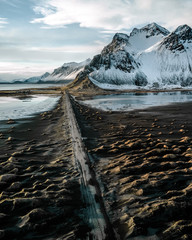 Aerial of Stokksnes black sand beach and ash road in Iceland leading to a mountain in the distance during sunset