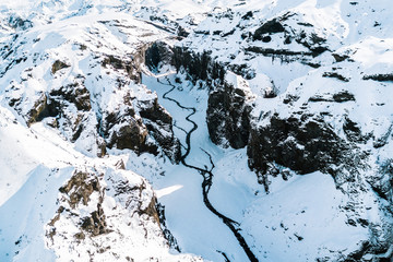 Aerial Snowed in Canyon with river in the Icelandic highlands during sunrise