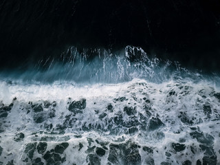 Abstract aerial of a cinematic crashing wave on a beach on Madeira, Portugal