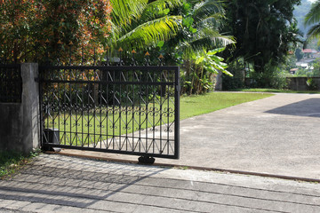Metal entry Gate. Green garden and Sunny day.