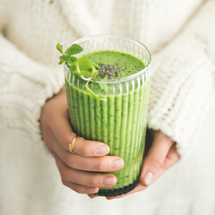 Matcha green vegan smoothie with chia seeds and mint in glass in hands of female wearing white sweater, square crop. Clean eating, detox, alkaline diet, weight loss concept