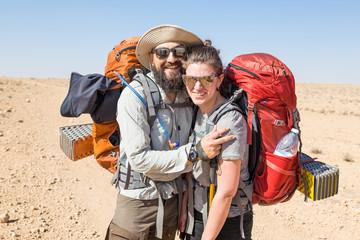 Happy couple backpackers hugging laughing, Negev desert, Israel.