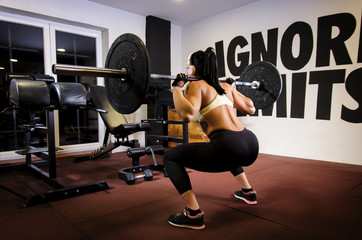Back view, strong female doing squats with heavy weights in the gym