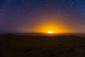 Night sky stars over desert hills sunset light.