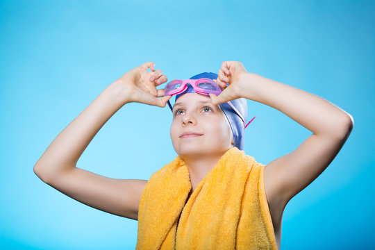 Girl swimmer in a bathing cap and glasses. The girl holds glasses for diving. She looks up.