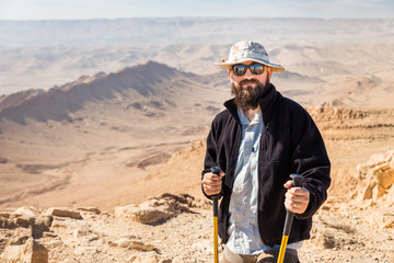 Fototapete - Bearded tourist backpacker standing desert mountain summit peak portrait.