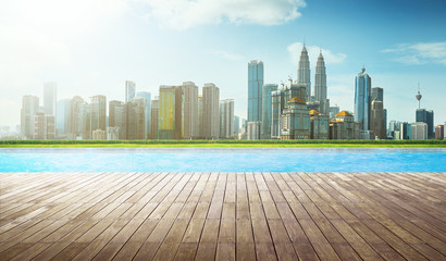 Wooden perspective brown empty floor in front of swimming pool with city skyline background .