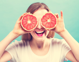 Happy young woman holding grapefruits on a blue background
