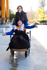 Disabled boy in wheelchair running  with caregiver outdoors
