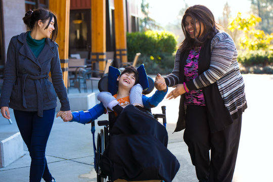 Disabled boy in wheelchair holding hands with caregivers on walk