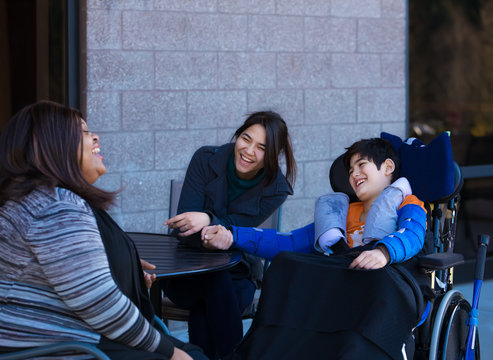 Disabled boy in wheelchair at table outdoors talking with caregivers