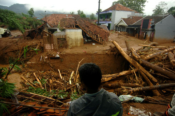 A villager stands near damaged houses after a landslide hit Pasir Panjang village in Brebes