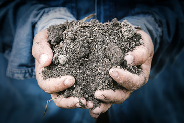 soil in farmer hands macro image with selective focus