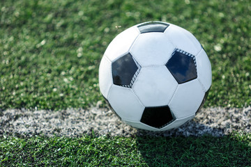 classic black and white football ball and prize for the best player  lies on the green field on the stadium