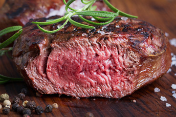 grilled cut beef steak with rosemary and seasoning on wooden board