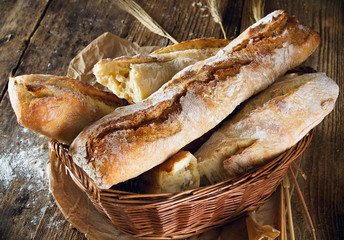 basket with fresh baked bread on wooden background