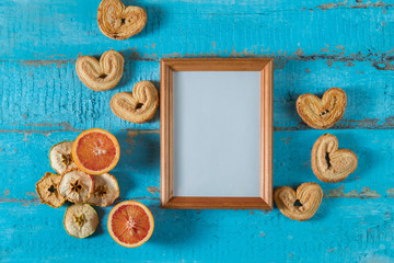 wooden photo frame on blue wooden surface texture with empty place for text or image with slices of dried apple, red orange