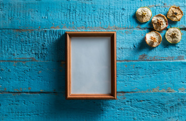 wooden photo frame on old blue wooden textured wall with empty place for text or image with slices of dried apple design