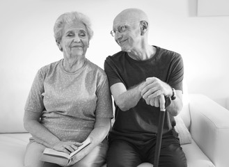 Senior people sitting on couch at home, black and white effect. Elderly care