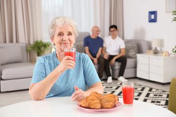 Senior woman having breakfast at home. Elderly care