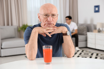 Senior man with glass of juice at home. Elderly care