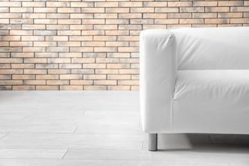 Stylish sofa near brick wall indoors