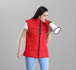 Young woman in red vest with megaphone on grey background