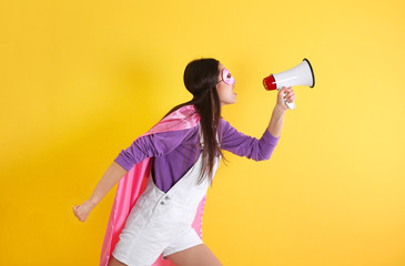Young woman in superhero costume with megaphone on color background