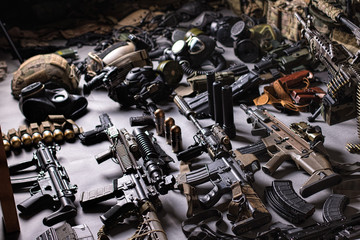 A lot of rifles, guns, grenades, helmets, gas masks, ammunition, vests, devices and other military gear.