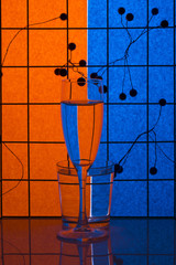 Still life with glass objects on a colored background