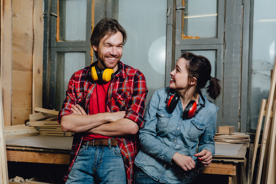Portrait of carpenters in the workshop. A man and a girl, leaned back and posed.