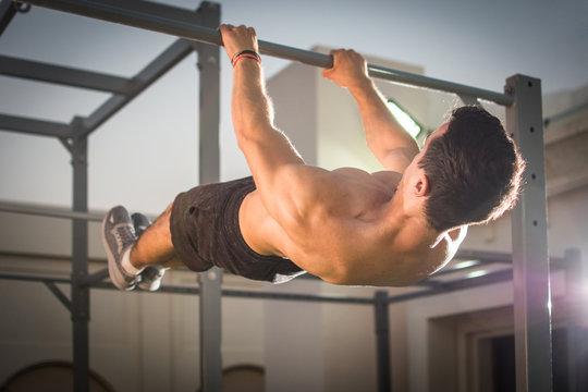 Handsome muscular man doing exercises on horizontal bar outdoors. Calisthenics workout.