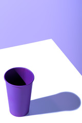 purple plastic disposable cup, on white surface with copy space
