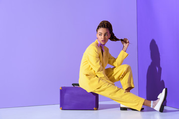 Fototapeta african american girl posing in yellow suit sitting on purple suitcase, on trendy ultra violet background obraz