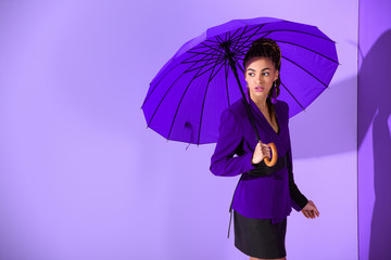 stylish african american girl posing with purple umbrella at ultra violet wall