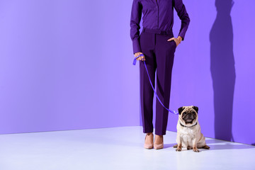 cropped view of girl posing in purple suit with pug, ultra violet trend