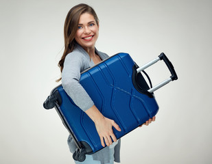 Smiling woman holding dark blue suitcase for travel.