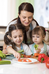 Cute mom and her kids making vegetable salad
