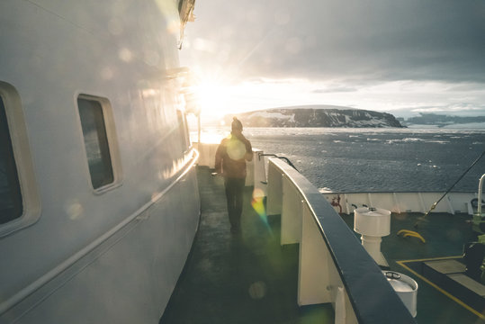 Man walking on a Ship towards the Sun - Antarctica.