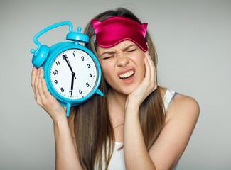 Upset surprised woman wearing seeping mask holding alarm clock.