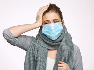 Sick woman wearing medical mask touching head.