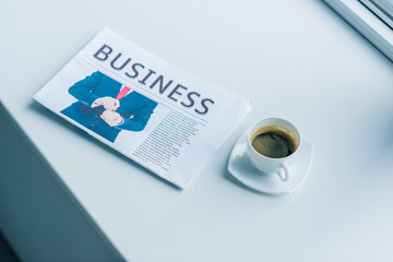 close up view of cup of coffee and business newspaper on white surface