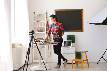 Young woman with professional camera preparing still life composition indoors