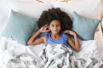 Cute African American girl in bed
