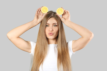 Funny young woman with slices of ripe lemon on grey background