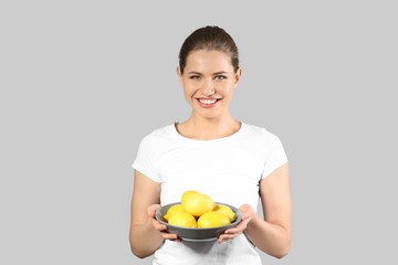 Beautiful young woman with ripe lemons on grey background