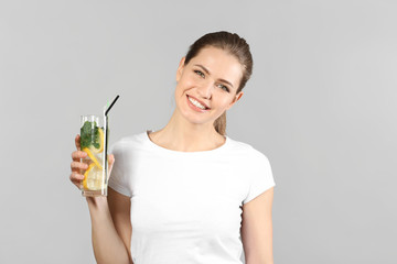Beautiful young woman with glass of lemonade on grey background