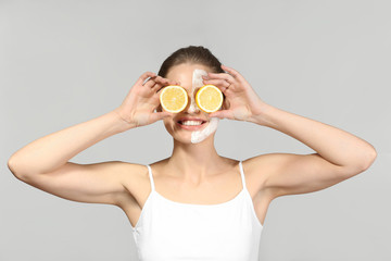 Young woman with facial mask and slices of ripe lemon on grey background
